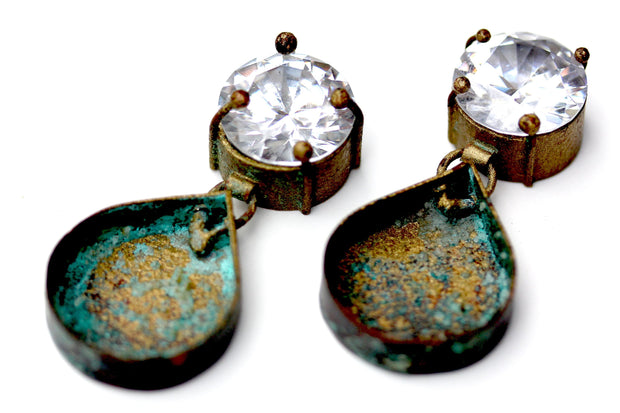 A pair of earrings with a sparkling CZ on top and an blue and gold colored Patina on a tear drop shape dangle.