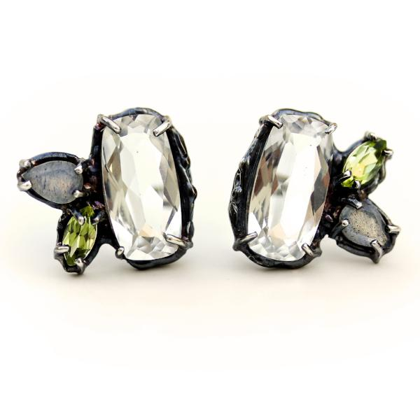 Slightly asymmetric stud earrings with white topaz, peridot and labradorite clustered together in an organic blackened sterling silver setting.
