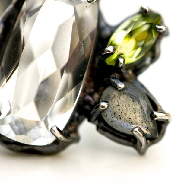 Detail photo of an earring with white topaz, peridot and labradorite prong set in blackened sterling silver.