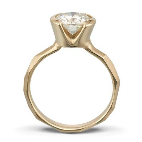Side view of a Modern 14k yellow gold Engagement Ring with a Partial Bezel, allowing light to shine through the Moissanite Stone.
