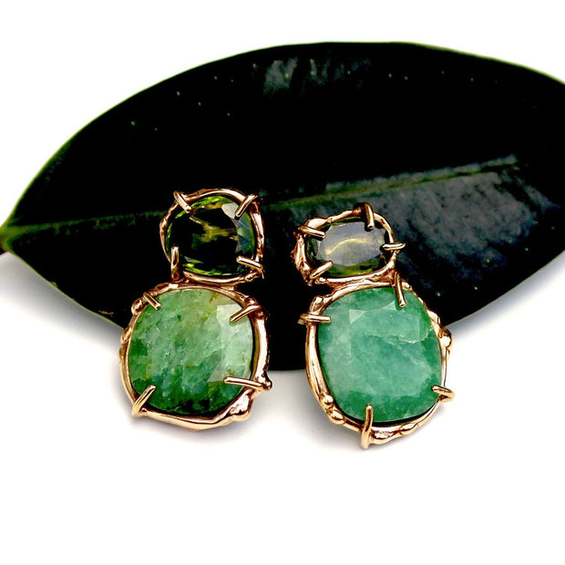 Emerald and peridot stud earrings in gold that have a refined organic quality.
