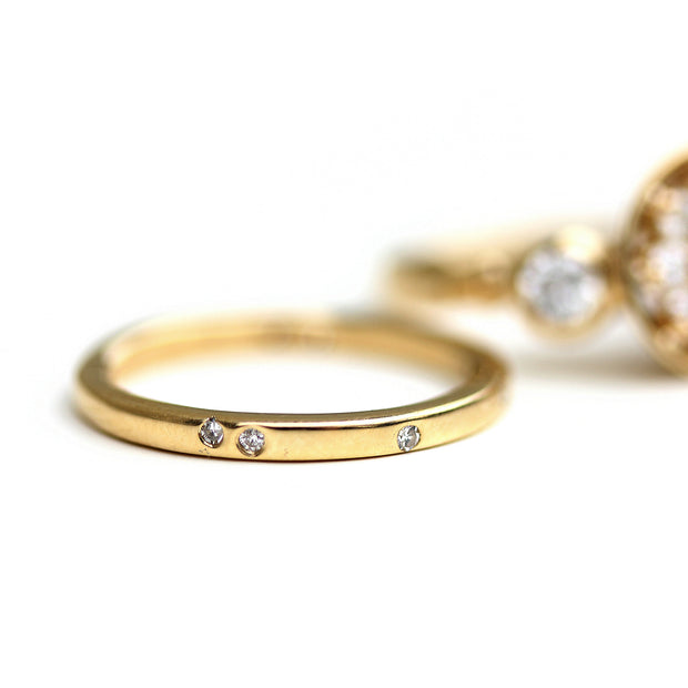 ethically made wedding band, flat style with scattered diamonds flush set or embedded into the surface.