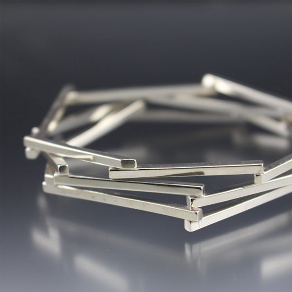 A stack of silver bangle bracelets that resemble a geometric bird's nest.