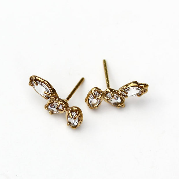 Stud earrings made of three marquise shaped white topaz stones set with organic prongs in gold.