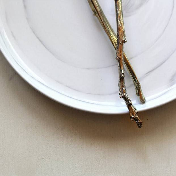 Detail of handles on handmade Sterling and Brass Cake Servers with Branch Handles and Hammered Texture.