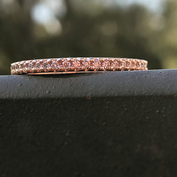 close up view on railing of rose gold and diamond wedding band