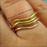 Two wave-like rings stacked together on a woman's finger, one is yellow gold and one is rose gold