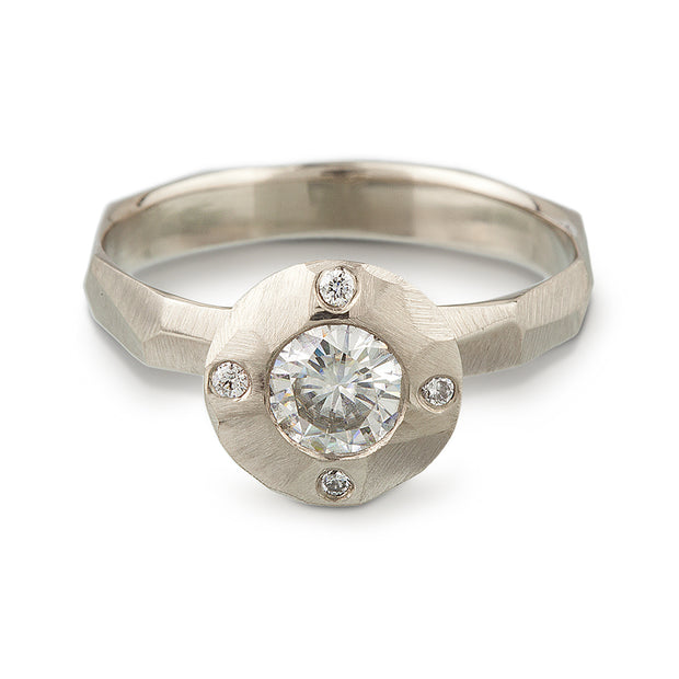 A contemporary take on a halo style engagement ring featuring a center Moissante and 4 small stones in North, south, east west positions