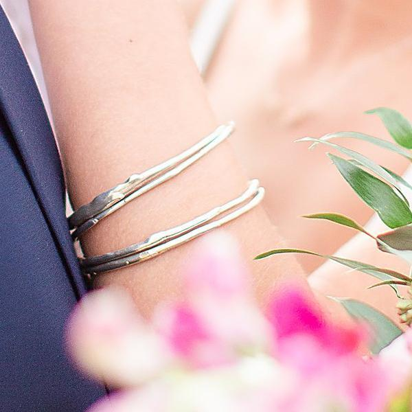 A detail photo of a woman's arm wearing a stack of sterling silver bangle bracelets that have a smooth organic texture that looks as if they are twigs covered in ice.