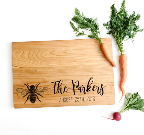 Personalized cutting board with bee and last name.