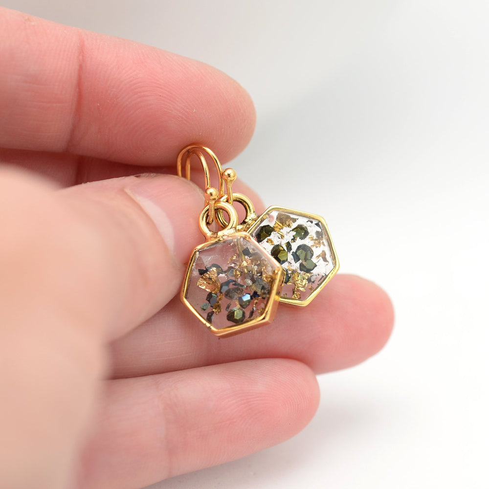 Gold abalone hexagon earrings in hand