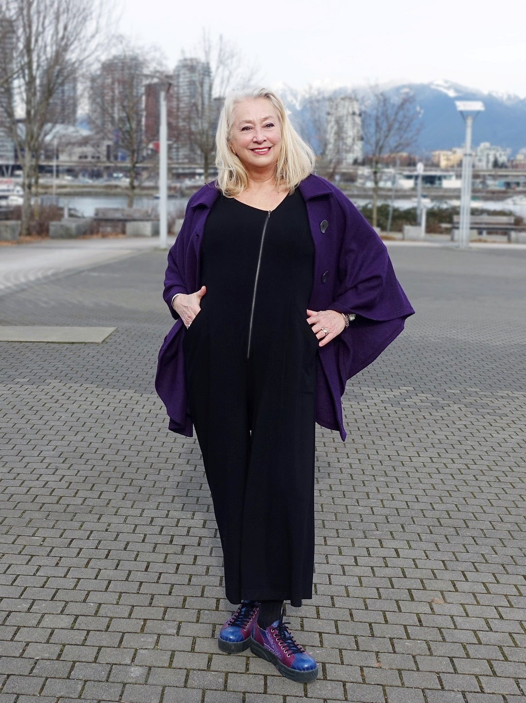 silver haired model wears a purple cape and outfit by designer Diane Kennedy