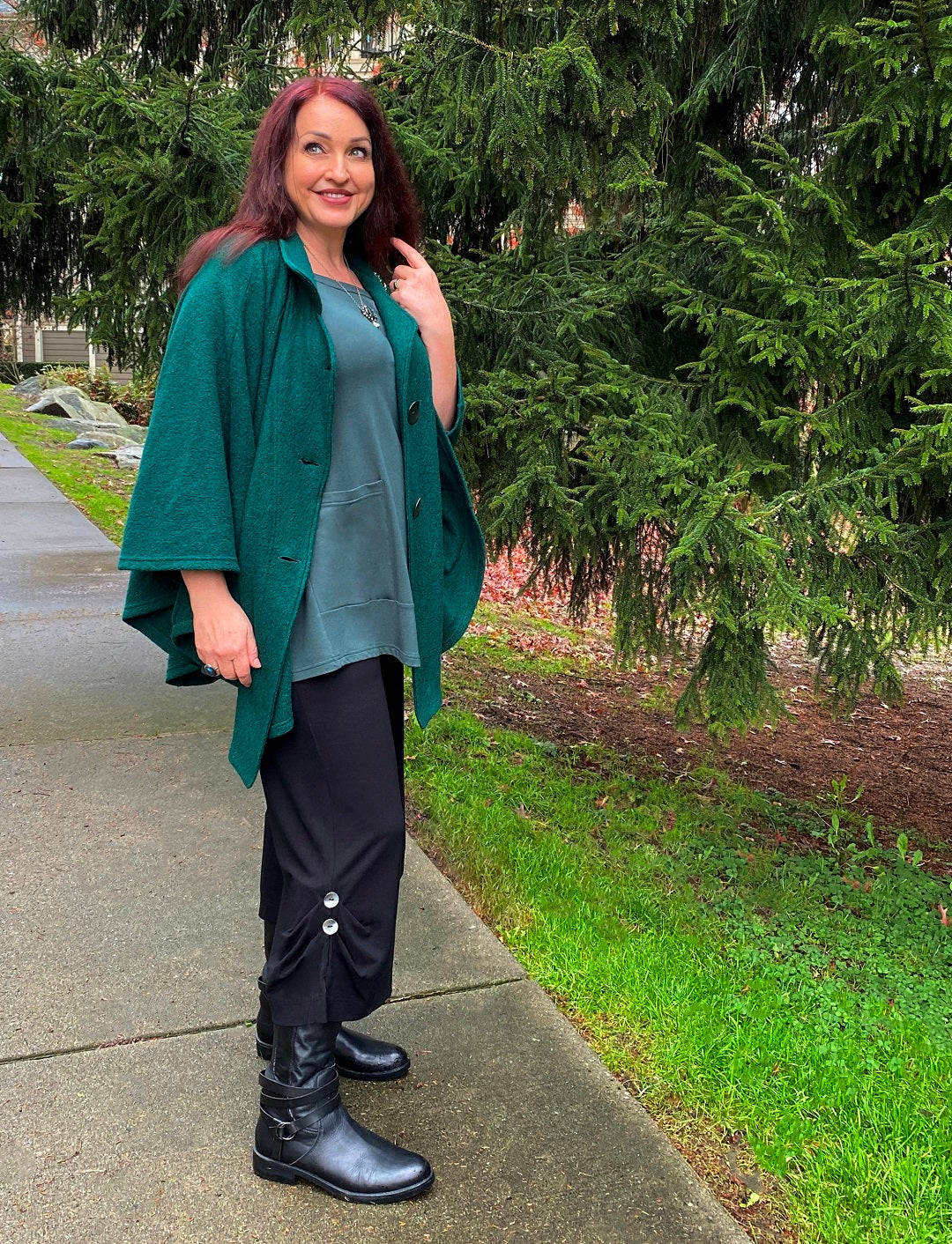 model wears a Diane Kennedy outfit of the Evergreen Cape over a Pine Tempo Tunic and Black Pier Pants