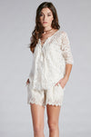 Model is wearing the Marilyn Lace Silk Shorts in white with a white lace top.