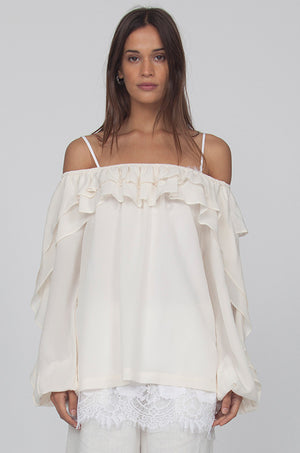 Model is wearing the Double Ruffle Silk Top in off white with the Coco Lace Silk Straight Cami in white peeking out from the hem of the ruffle top. Also worn with the Wide Leg Linen Belted Pants in dove.