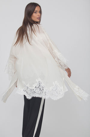 Model is wearing the Coco Lace Silk Kimono in off white, opened, with the Gigi Lace Silk Cami in white underneath with wide leg pants that are black with vertical white stripes on the sides.