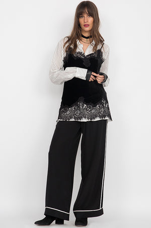 Model is wearing the Wide Leg Silk Pants in black with white piping, along with a striped button up top and the Anastasia Lace Trim Velvet Cami in black on top. Also worn with pointed toe, black ankle boots.
