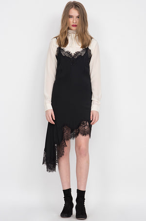 Model is wearing the Emma Lace Silk Slip Dress in black with a long sleeve, silk, turtleneck blouse in dove underneath. Also worn with black high heel ankle boots.