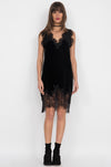 Model is wearing the Anastasia Lace Velvet Dress in black with lower calf, black suede high heeled boots.