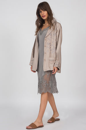 Model is wearing the Grace Lace Silk Dress in steeple grey with the Silk Pajama Shirt in camel on top, opened. Also worn with brown, flat, open toe, slip-in sandals.