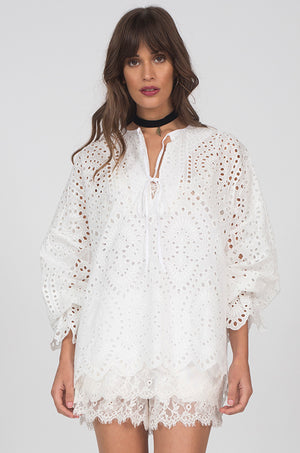 Model is wearing the Adele Cotton Oversized Top in white. Worn with the Floral Lace Cami in white and Coco Lace Shorts in white.