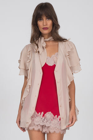 Model is wearing the Ruffle Self-Tie Top in nude, worn opened, with the Marilyn Lace Silk Cami in red with sand shell lace. Worn with matching Marilyn Lace Silk Shorts.