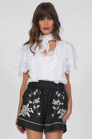 Model is wearing the Ruffle Self-Tie Top in white, with the Coco Lace Silk Cami in dove underneath. Also worn with the Emily Embroidered Silk Shorts in black.