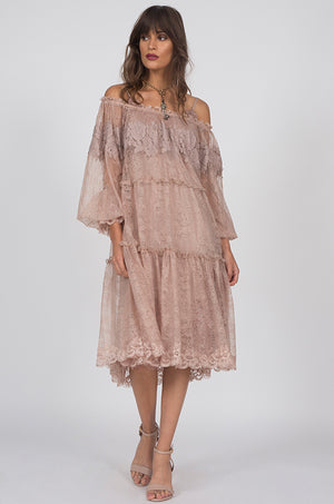 Model is wearing the Chantilly Peasant Lace Dress in sand shell with nude colored, open toe, ankle strap high heels.