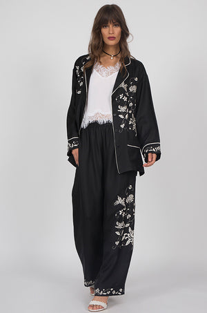 Model is wearing the Emily Silk Embroidered Pants in black with the Lucy Crop Cami in white and the Emily Embroidered Silk Kimono in black on top, open. Also worn with open toe, ankle strap, white high heels.