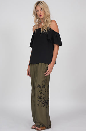 Model is wearing the Emily Silk Embroidered Pants in olive with the Off-Shoulder Silk Cami Top in black. Also worn with brown, flat, open toe, slip in sandals.
