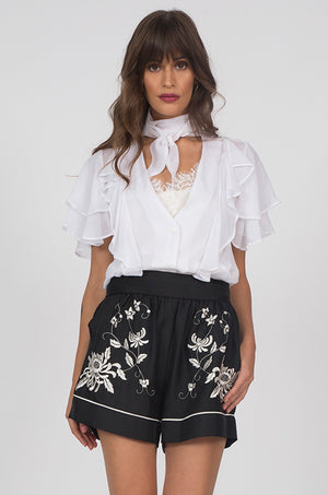 Model is wearing the Emily Embroidered Silk Shorts in black with the Ruffle Self-Tie Top in white.