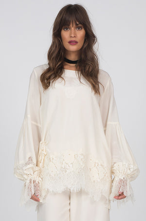 Model is wearing the Romantic Lace Sleeve Silk Top in white with the Julia Lace Silk Pants in dove.