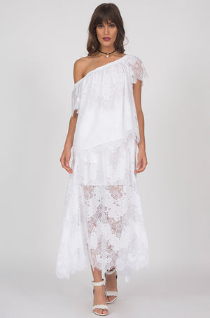 Model is wearing the Suzy Zig Zag Lace Skirt in white with the Julia Lace Silk Off The Shoulder Top in white and open toe, ankle strap, white high heels.
