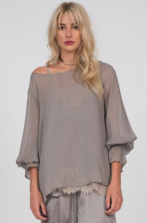 Model is wearing the Sheer Silk Smock Cuff Shirt in steeple grey with the Coco Lace Silk Straight Cami in steeple grey with birch lace underneath. Also worn with the Hammered Silk Belted Pants in steeple grey.