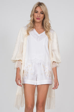 Model is wearing the Emma Lace Jacquard Robe in dove, opened and scrunched sleeved, with the V-Neck Linen Pocket Tee in white underneath the Lucy Crop Cami in white, and the Emily Embroidered Silk Shorts in dove.