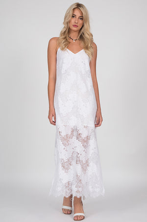 The Suzy Zig Zag Lace Dress in white, worn with open toe, ankle strap, white high heels.