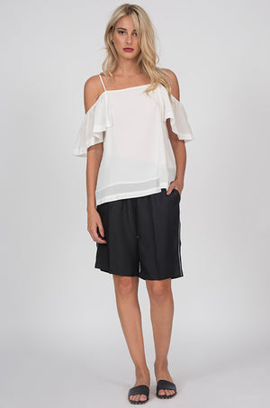 Model is wearing the Silk Twill Piping Shorts in black with the Off-Shoulder Silk Cami Top in dove. Also worn with black, open toe, flat, slip in sandals.