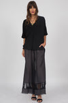 Model is wearing the Capri Lace Linen Pants in black with a black v neck wrap tee and open toe, ankle strap high heels.