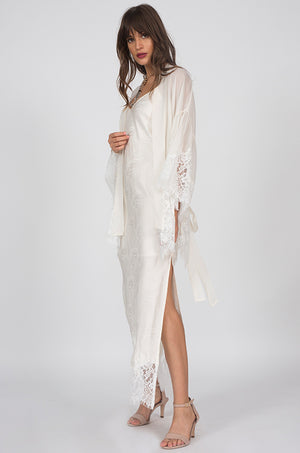 Side View to show slit; Model is wearing the Emma Silk Jacquard Slip Dress in dove with the Coco Silk Lace Kimono in dove. Also worn with open toe, ankle strap, nude colored high heels.