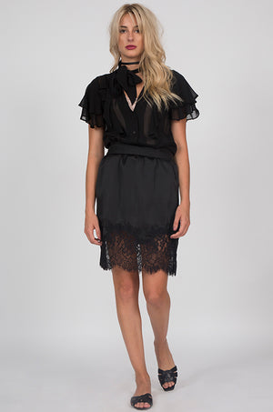 Model is wearing the Hammered Silk Lace Skirt in black with the Ruffle Self-Tie Top in black and the Coco Lace Silk Straight Cami in white underneath. Also worn with flat, black, open toe, slip in sandals.