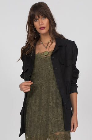 Model is wearing the Linen Army Jacket in black with an olive dress.