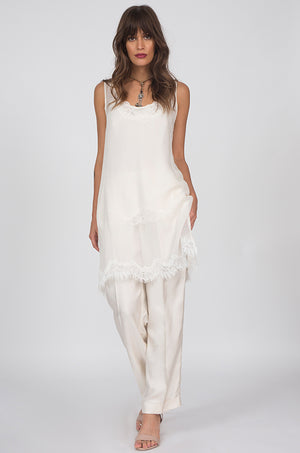 Model is wearing the Sheer Silk Tank Top in white, worn without the matching sash, along with the Floral Lace Silk Cami in white underneath. Also worn with the Silk Twill Piping Pants in dove.
