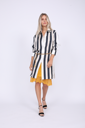 Model is wearing the Bold Stripe Sleeve Dress in black, mostly buttoned, with the Coco Lace Bodice Lace Dress in gold underneath and a gold chain used as belt. Also worn with black, ankle strap, open toe high heels.