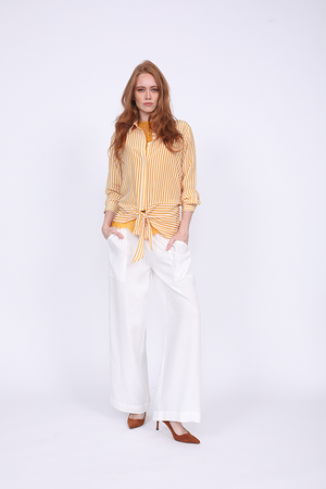 Model is wearing the Mini Stripe Shirt in gold with the Zoe Coco Camisole in gold underneath, and the Tencel Cargo Wide Leg Pant in white. Also worn with reddish orange, pointed toe, kitten heels.