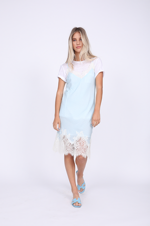 Model is wearing the Anne Marie Silk Dress in baby blue/off white with the Crew Neck Linen Tee underneath, with the sleeves cuffed, and baby blue flat sandals.