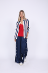 Model is wearing the Hayley Wide Leg Snap Pant in navy with the Double Silk Solid Cami in Red and the Bold Stripe Shirt in navy, worn unbuttoned.