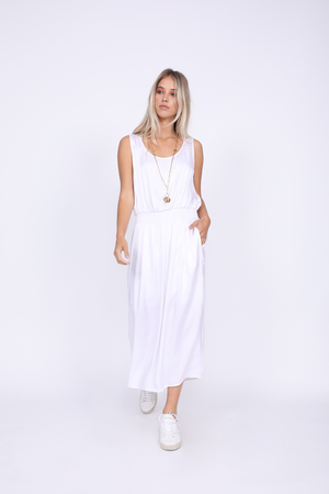 Model is wearing the Hayley Tank Dress in bright white with white sneakers (no socks) and a gold colored, long necklace.
