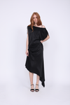 Model is wearing the Hayley Asymmetric Shoulder Dress in black, unbelted, and with open toe, ankle strap, black high heels.