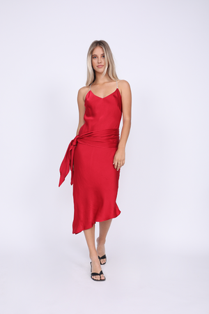 Model is wearing the Aimee Slip Dress in fiery red with matching sash worn wide on the waist. Also worn with sandals.