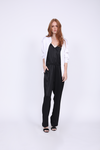 Model is wearing the Hayley Jumpsuit in black with the Megan Camisole in black/dove underneath, and the Hayley Bomber Jacket in bright white on top, worn unzipped.